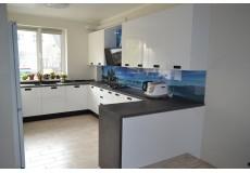 Белая глянцевая кухня с темной столешницей и черными ручками